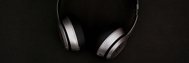 silver headphones on top of black surface